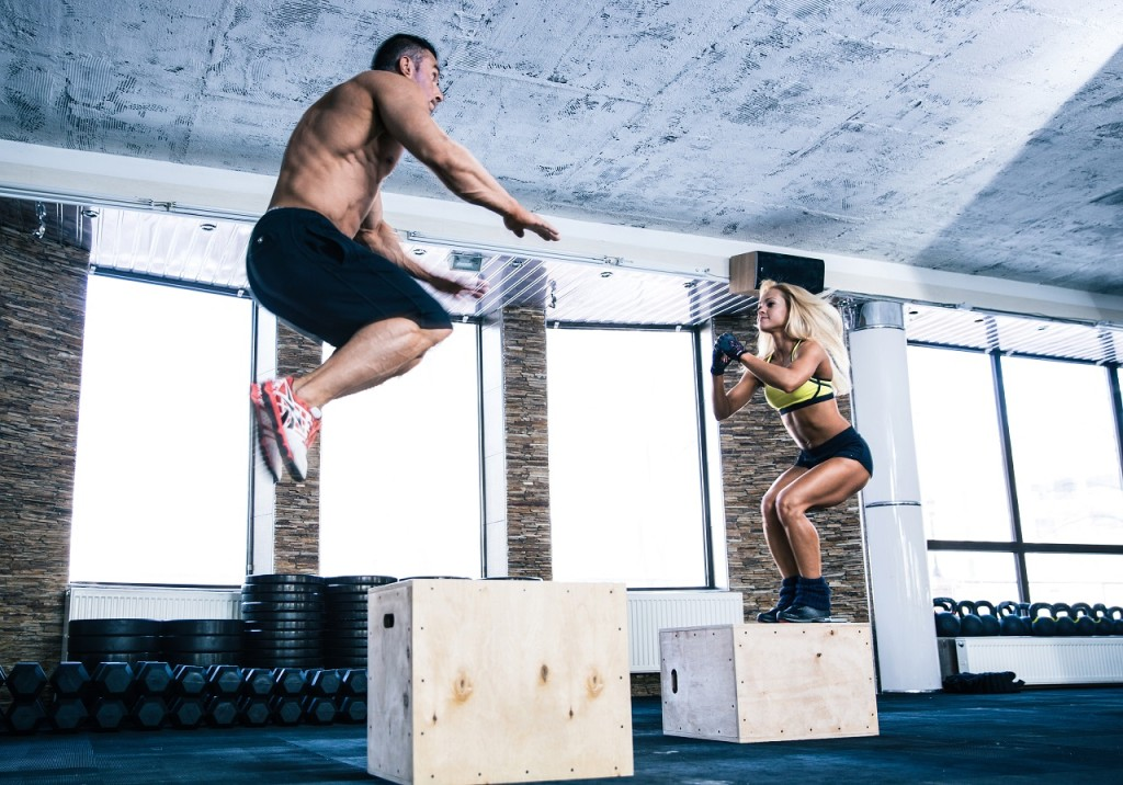 Man and woman jumping on fit box at gym